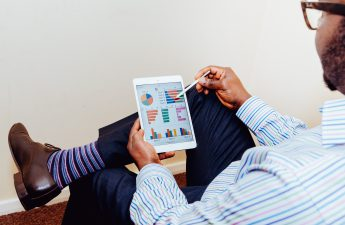 man looking at property management software reports on tablet