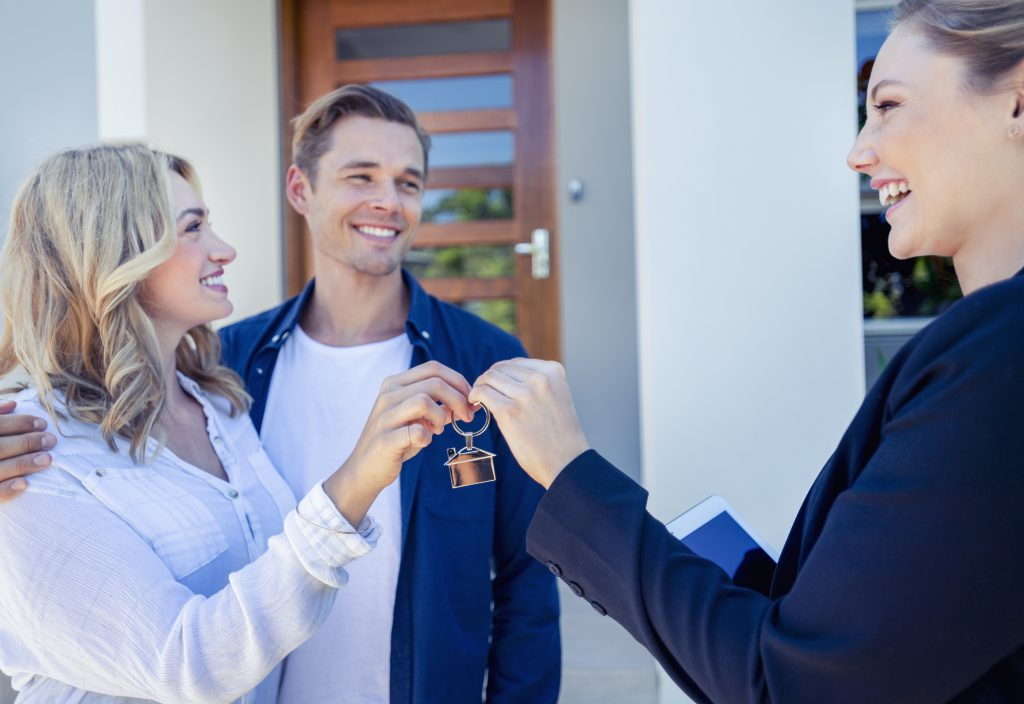 A landlord handing over a set of keys to her new tenants.