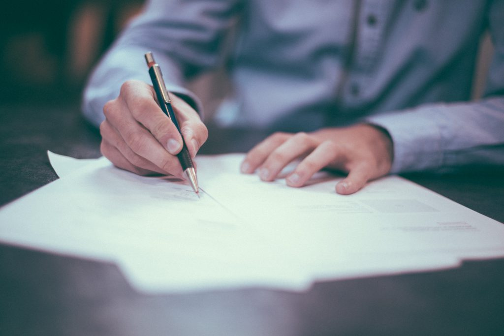man signing legal documents on desk