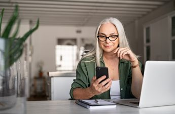 property-manager-sitting-at-table-with-laptop-while-using-smartphone