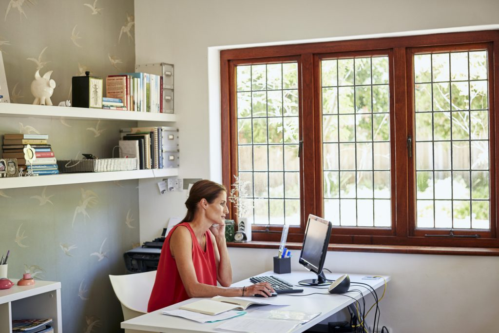 woman-sitting-in-home-office-at-desk-with-monitor-and-landlord-paperwork