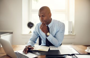 landlord-sitting-at-desk-with-laptop-and-papers-while-looking-at-tenant-screening-reports-online