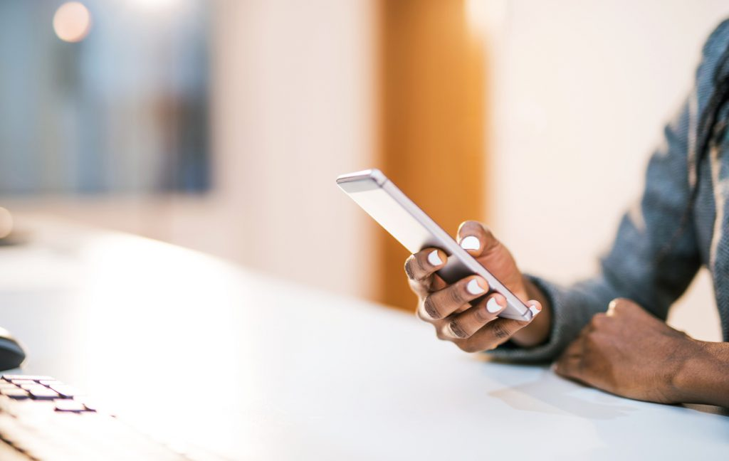 person-sitting-at-counter-while-using-smartphone