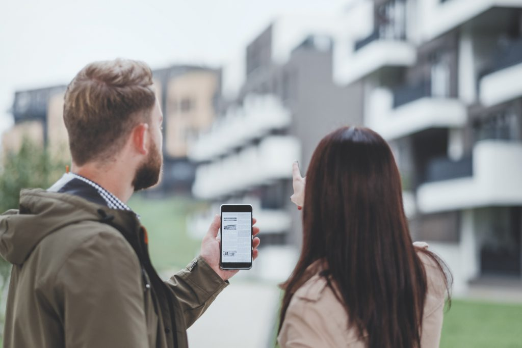 man-and-woman-looking-at-apartment-complex-while-using-online-listing-displayed-on-smartphone