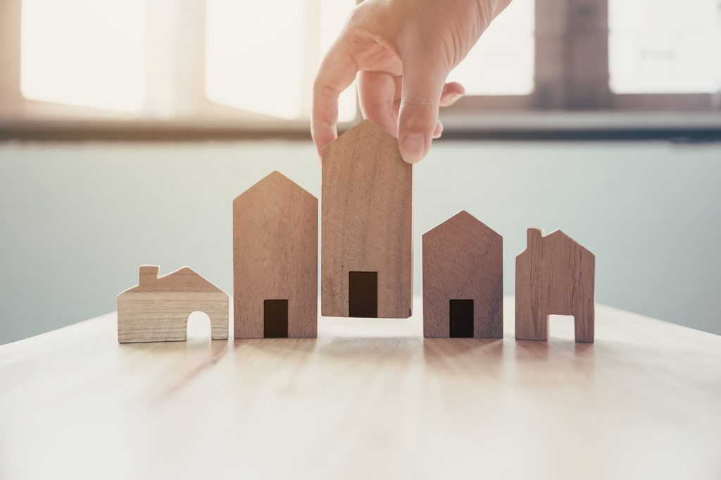 hand-placing-wooden-house-models-in-a-row-on-table-near-windows