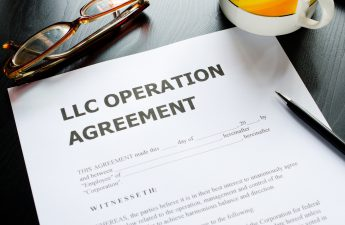llc-operation-agreement-paperwork-on-desk-with-glasses-mug-and-pen