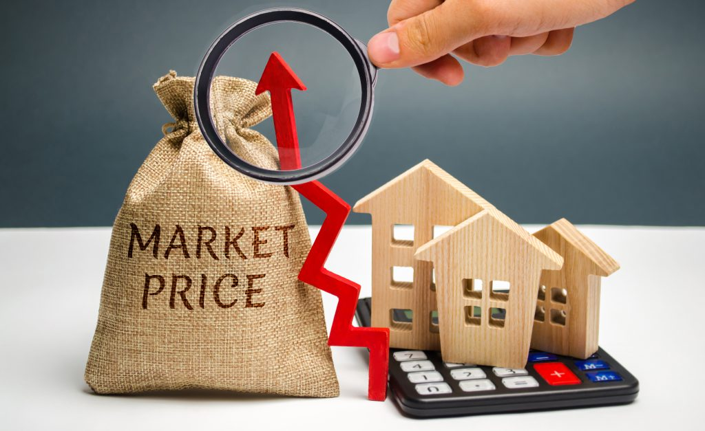 Calculating Cap Rate market price growth. Market price and an up arrow with a calculator and wooden houses. The concept of increasing housing prices. Rising rent. Real estate market growth.
