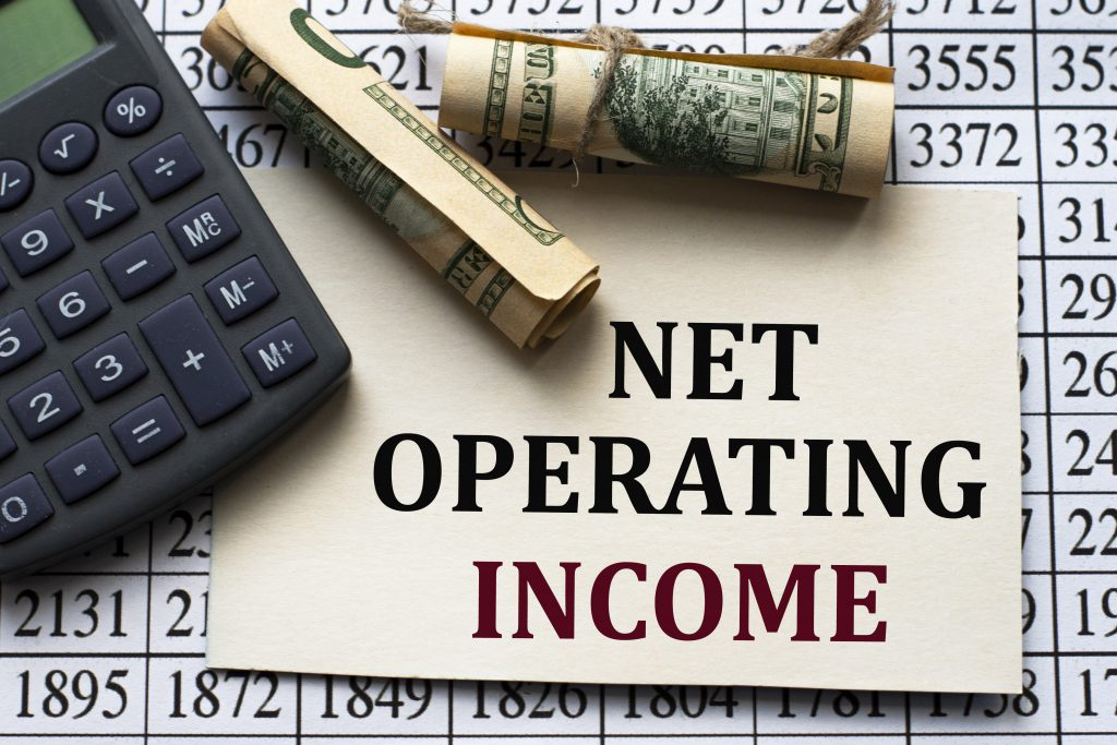 Calculating Cap Rate for NET OPERATING INCOME - words on white paper against the background of a table of numbers with a calculator and banknotes. Business and finance concept