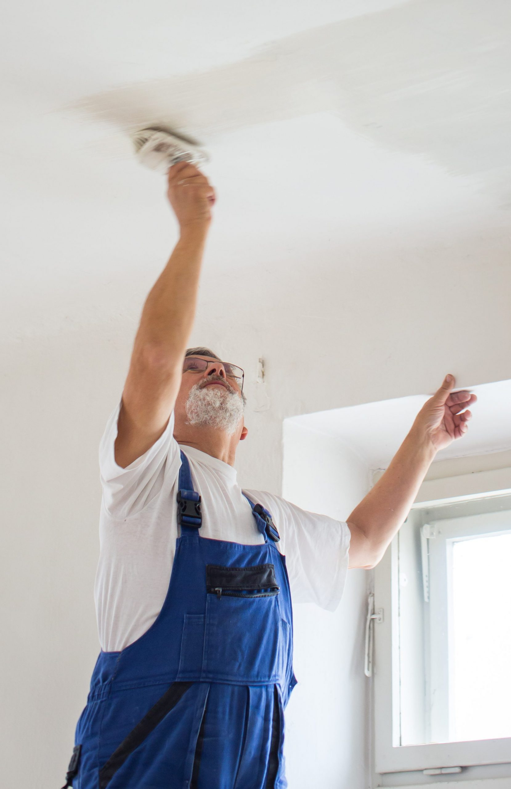 Senior man paintinga room of rental appartment with a paint bucket, wall painting concept - short time rental property maintenance
